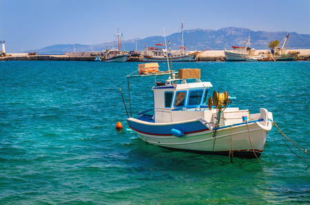 sea fishing: Small blue-white boat floating on clear water of Aegan sea on Greek coast, Kos, Greece
