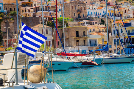 aegean: Blue white Greek flag and wind in Greek port full of boats, Kos, Greece