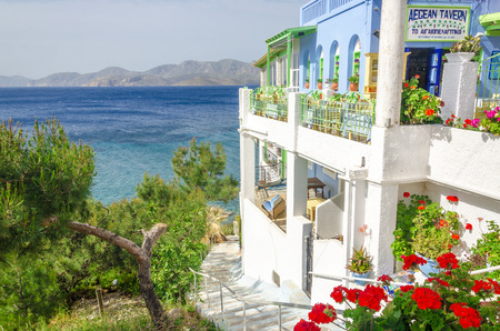 KALYMNOS, GREECE - MAY 01, 2015: Panoramic view on typical Greek restaurant with flowers and white teracce having clear view on sea landspace with islands, Greece