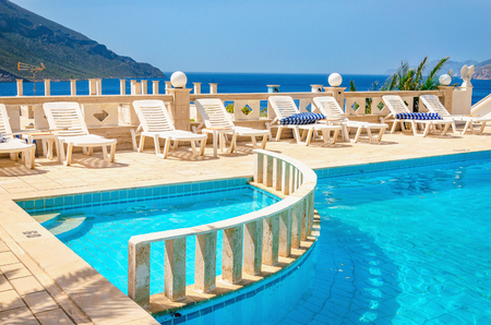 Amazing view on swimming pool area and sunbeds under blue sky with amazing view on coast and sea in background in sunny summer day, Greece Editorial