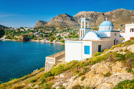 monastery nature: View on iconic white church with blue domes by the sea coast on Greek island, Kalymnos, Greece