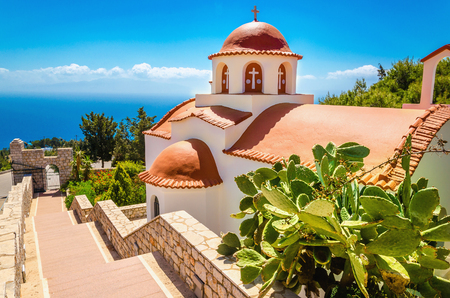myconos: Typical Greek church with red roof and green plants in front and sea view in the background. Greece