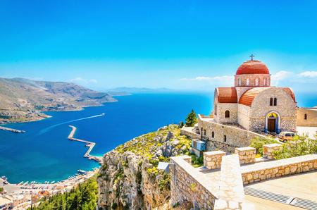 Prachtig uitzicht op de afgelegen kerk met rode daken op de klif van de zee, Griekenland