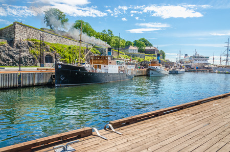 OSLO, NORWAY - 21 JUNE, 2015 - Old fishing boat and Akershus Fortress seen from wooden pier od Oslo Fjord, Oslo, Norway