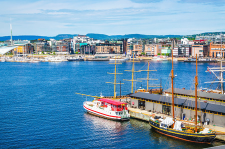 OSLO, NORWAY - 21 JUNE, 2015 - A transport ship moored in the harbor by a beautiful modern Aker Brygge, Oslo Fjord, Oslo, Norway, Scandinavia