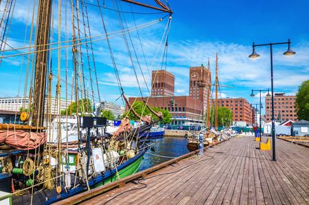 前景、オスロ、ノルウェーのスカンジナビアの美しい帆船と桟橋オスロ ・ フィヨルドから見た美しい市庁舎 写真素材