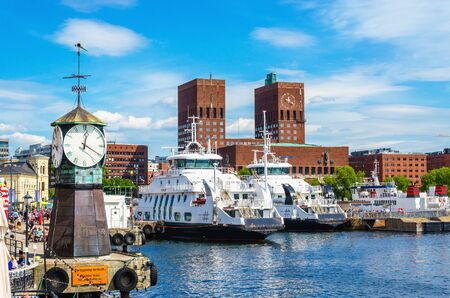 OSLO, NORWAY - 21 JUNE, 2015 - Clock on Aker Brygge Dock, modern and very popular part of Oslo in the background of the famous Oslo City Hall and the harbor, Oslo Fjord, Norway, Scandinavia