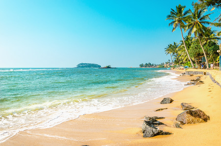 Mooi exotisch strand met gouden zand en hoge palmbomen tegen de azuurblauwe zee en de blauwe hemel, Caribische eilanden Stockfoto