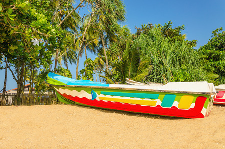 Colorful exotic boat on an exotic beach full of beautiful tall palm trees Stock Photo