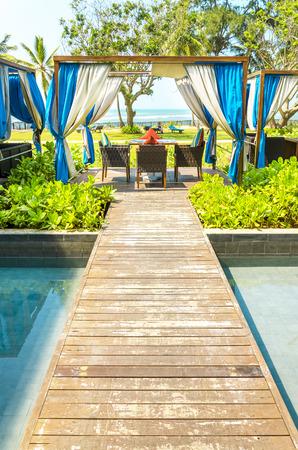 Prachtige luxe resort met een geweldige plek voor zonnen in de tuin van het hotel, ligstoelen op kleine eilanden in het zwembad, Sri Lanka, Azië