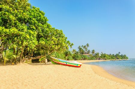 Beautiful wild and exotic Asian beach with colorful boat Stock Photo