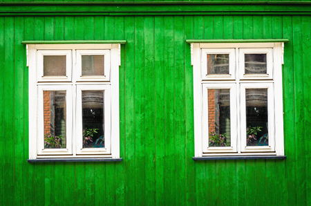 White wooden window against a green wooden front of an old beautiful house.