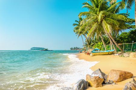 Mooie exotische strand vol palmbomen tegen de azuurblauwe zee en de blauwe hemel Stockfoto