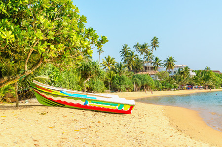 Beautiful wild and exotic Asian beach with colorful boat, Sri Lanka Stock Photo