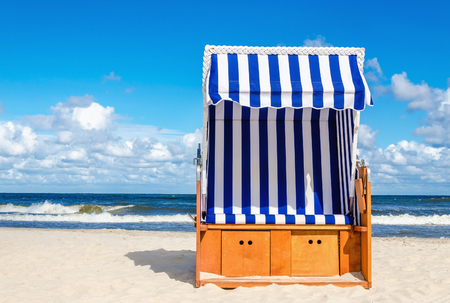 노란색 모래 Kolobrzeg 해변, 발트 해, 폴란드에 파란색과 흰색 위커의 자