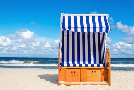 Blauw en wit rieten stoel op geel zand strand Kolobrzeg, Oostzee, Polen Stockfoto