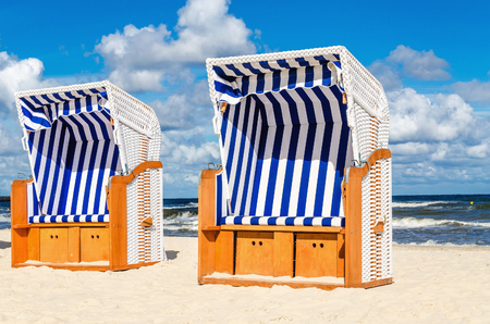 Blue and white wicker chairs on sandy Kolobrzeg beach, Baltic Sea, Poland Stock Photo