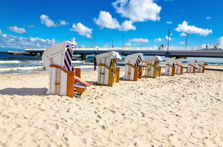 Beautiful sandy beach full of wicker chairs against a blue sky Stock Photo