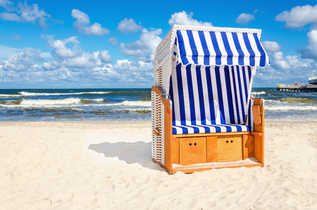 Blue and white wicker chair on sandy beach with cloud Stock Photo