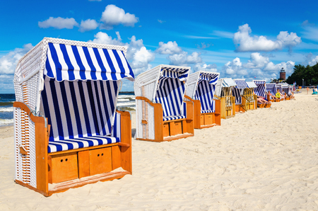 Blue and white wicker chairs on sandy beach, Baltic Sea