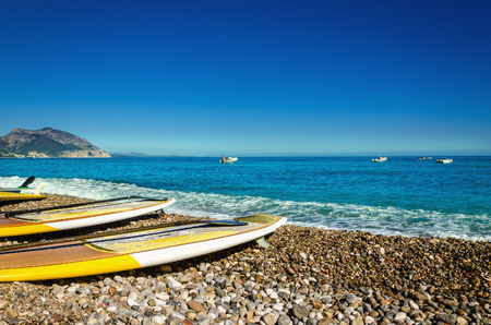 Yellow surfboards on the beautiful pebble beach, Golfo di Orosei, Sardinia, Italy