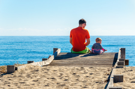 The father of a small child sitting on a pier staring at sea Stock Photo