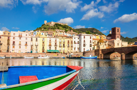 Colourful boat on background of beautiful buildings of Bosa, Sardinia, Italy Stock Photo