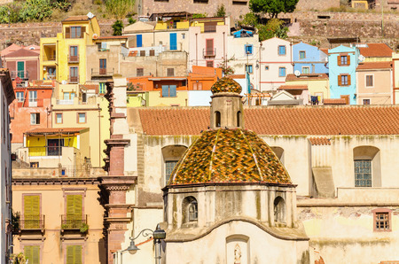 Beautiful dome on background of colorful buildings of Bosa, Sardinia, Italy