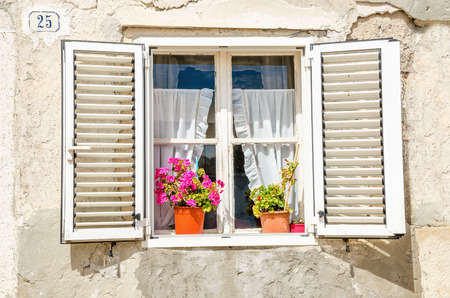 Picturesque window , shutters, colorful flowers against a white limestone wall Stock Photo