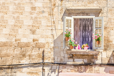 Window with flowers on the background of a white stone wall typical of architecture in Croatia Stock Photo