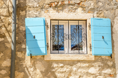 Picturesque window with blue shutters white limestone wall Croatia, Balkans
