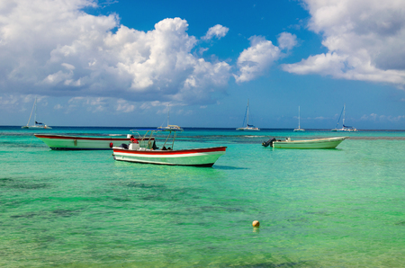Wooden colorful boats on the azure clear water of the Caribbean Sea on a background of blue sky with white clouds, Dominican Republic