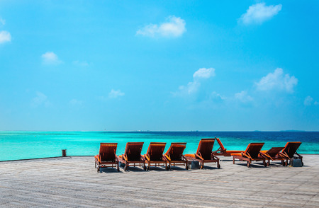 Wooden orange deck chairs on a pier on the background of the azure water of the Indian Ocean, Maldives