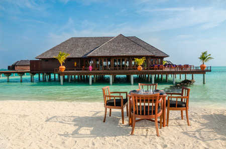 Table and chairs at restaurant at the background of water bungalows, Maldives island Stock Photo