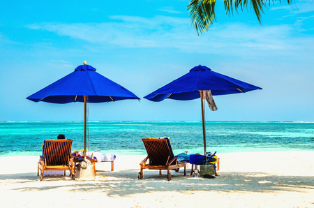 Blue umbrellas and wooden couches on a sandy beach