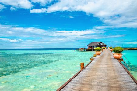 Houten brug die leidt tot een exotische bungalow op de achtergrond van azuurblauw water, de Maldiven
