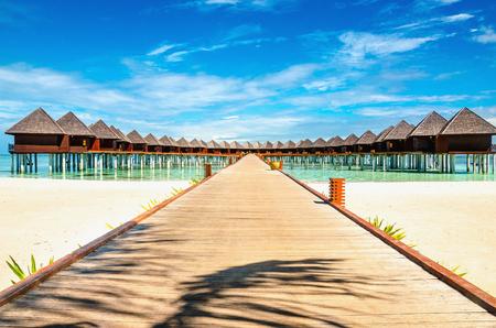 Pont en bois menant à un bungalow exotique sur le fond de l'eau azur, maldives