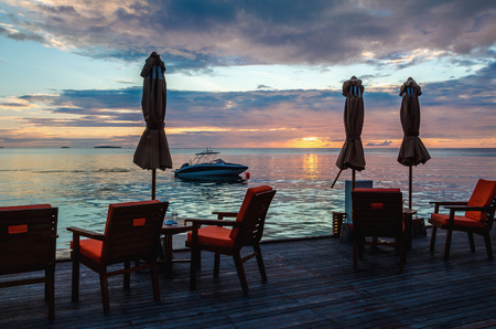 Restaurant on the water on the background of beautiful colorful sunset over the ocean 스톡 콘텐츠