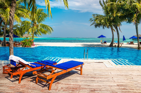 Wooden deck chairs by the pool on the background of the azure ocean water, Maldives