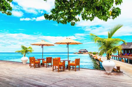 Restaurant met parasols op een houten pier tegen het azuurblauwe water van de oceaan