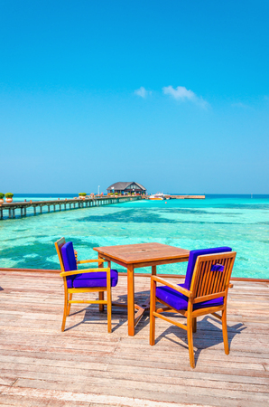 Tables and chairs in a wooden restaurant on stilts on the background of azure water and sunny sky Stock Photo