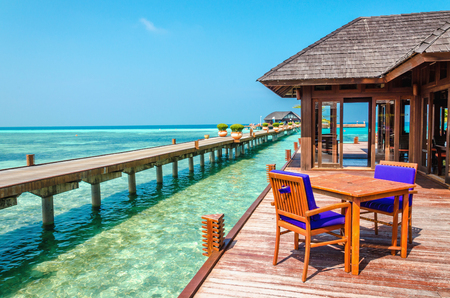 An exotic view of a wooden restaurant on stilts on a background of azure water and sunny sky