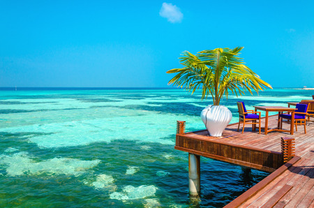 An exotic view of a wooden restaurant on stilts on a background of azure water and blue sky