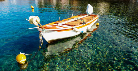Old boat in blue green sea water photo