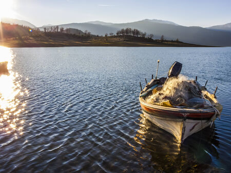 Sunset at Plastiras lake with a boat in central Greece