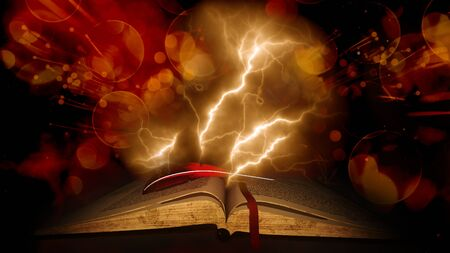 light beams: Vintage old book with feather pen on bokeh background with thunderbolt