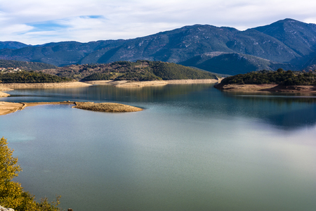 and arcadia: Ladonas artificial lake in Arcadia, Greece against a blue sky with clouds, and mountains as background