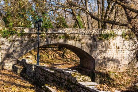 and arcadia: Old vintage stone bridge with trees in Arcadia, Greece. Stock Photo