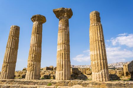 valley of the temples: Ancient columns of Hercules Temple at Italy, Sicily, Agrigento. Greek Temples Valley with city background.