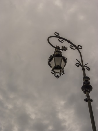 A retro lampost at a dark sky with clouds.
